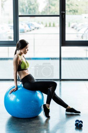 Photo for Attractive girl sitting on blue fitness ball near dumbbells - Royalty Free Image