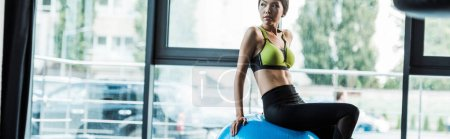 Photo for Panoramic shot of attractive girl sitting on blue fitness ball - Royalty Free Image