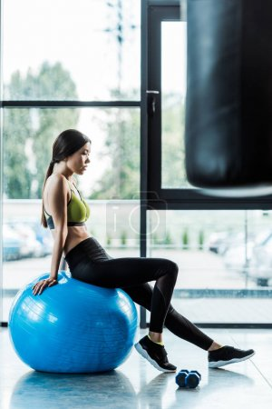 Photo for Selective focus of pretty girl sitting on blue fitness ball near dumbbells - Royalty Free Image