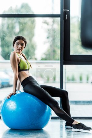 Photo for Selective focus of beautiful girl sitting on blue fitness ball near dumbbells - Royalty Free Image