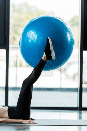 Photo for Cropped view of girl exercising with blue fitness ball on fitness mat - Royalty Free Image
