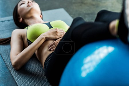 Photo for Selective focus of woman exercising with fitness ball on fitness mat - Royalty Free Image
