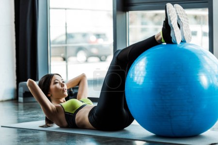Photo for Beautiful woman working out with fitness ball on fitness mat - Royalty Free Image