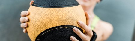 Photo for Panoramic shot of girl holding ball while training in gym - Royalty Free Image