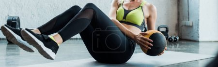 panoramic shot of girl exercising with ball on fitness mat