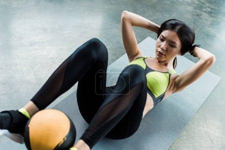 Photo pour Vue aérienne de la femme attirante s'exerçant avec la bille sur le tapis de forme physique dans la gymnastique - image libre de droit