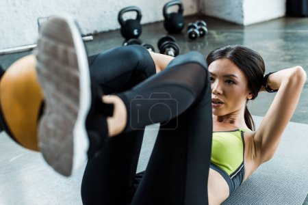 Photo for Selective focus of attractive woman exercising with ball on fitness mat in gym - Royalty Free Image