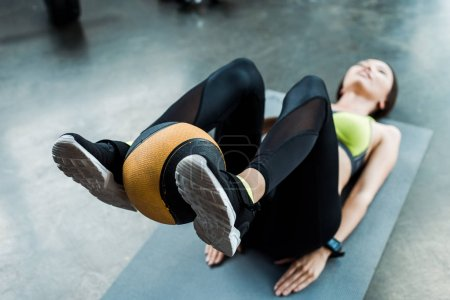 selective focus of young woman exercising with ball on fitness mat in gym