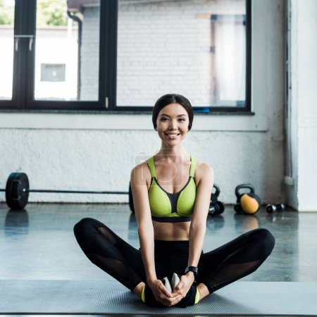 young happy woman stretching on fitness mat in gym