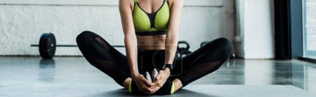 Photo for Panoramic shot of young woman stretching on fitness mat in gym - Royalty Free Image