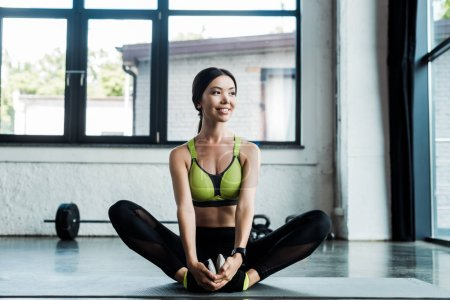 young positive woman stretching on fitness mat in gym
