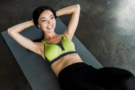 Photo for Happy girl doing do abs of fitness mat in sports center - Royalty Free Image
