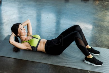 Photo for Young happy woman doing do exercise of fitness mat in sports center - Royalty Free Image