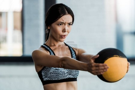 young sportswoman holding ball while exercising in gym