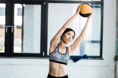 Photo for Attractive young sportswoman holding ball while working out in gym - Royalty Free Image