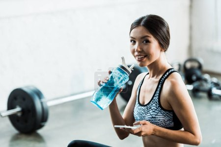 Photo for Cheerful sportswoman holding smartphone and sport bottle - Royalty Free Image