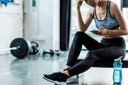 Photo for Cropped view of sportswoman sitting on step platform and using smartphone - Royalty Free Image