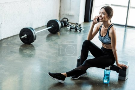 Photo for Cheerful sportswoman sitting on step platform and talking on smartphone - Royalty Free Image