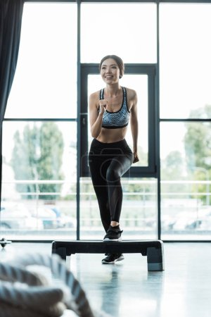 Photo for Selective focus of cheerful girl working out on step platform in sports center - Royalty Free Image