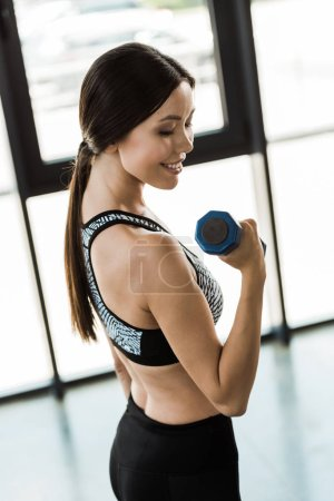 Photo for Happy girl exercising with dumbbell in sports center - Royalty Free Image