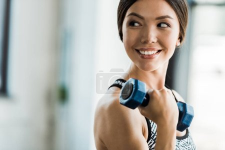 Photo for Happy and sportive girl exercising with dumbbell in sports center - Royalty Free Image
