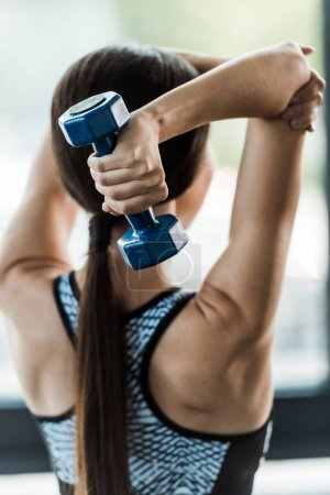 Photo for Back view of sportswoman working out with dumbbell - Royalty Free Image