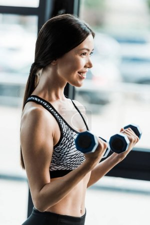 Photo for Positive and sporty woman holding dumbbells in gym - Royalty Free Image