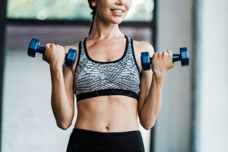 Photo for Cropped view of cheerful girl holding dumbbells - Royalty Free Image