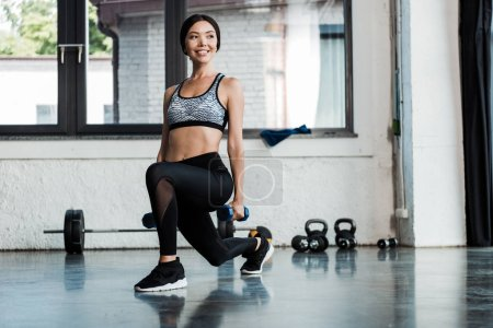 Photo for Cheerful sportswoman doing squat exercise with dumbbells - Royalty Free Image