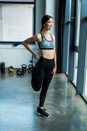 Photo for Happy girl stretching while warming up in gym - Royalty Free Image