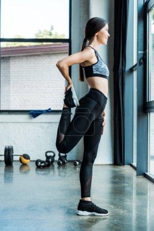 Photo pour Vue latérale de la fille s'étirant tout en s'échauffant dans la gymnastique - image libre de droit