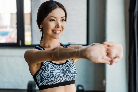 Photo pour Foyer sélectif de fille gaie étirement tout en se réchauffant dans la salle de gym - image libre de droit