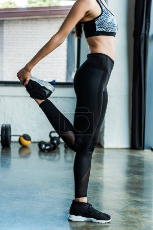 Photo for Cropped view of girl stretching while standing in gym - Royalty Free Image