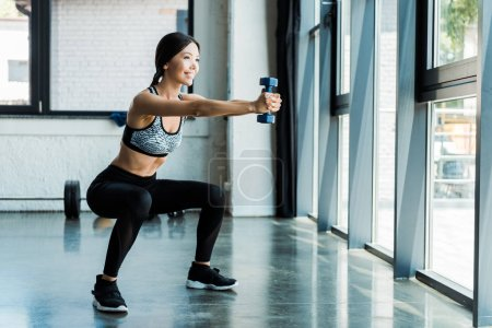Photo for Happy young sportswoman holding dumbbells and doing squat exercise - Royalty Free Image