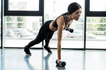 Photo for Young sporty woman exercising with dumbbells in gym near windows - Royalty Free Image