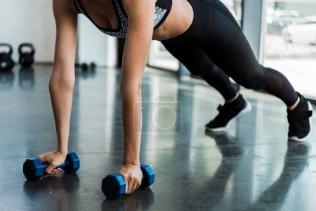 Photo for Cropped view of sporty girl exercising with dumbbells in sports center - Royalty Free Image