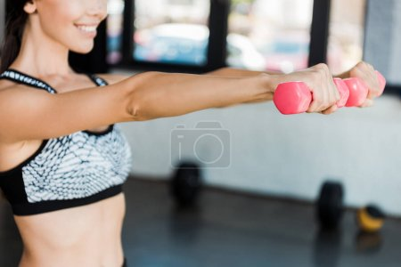 Photo for Cropped view of happy girl holding pink dumbbells while exercising in gym - Royalty Free Image