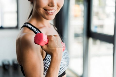 Photo for Cropped view of happy girl holding pink dumbbell in gym - Royalty Free Image