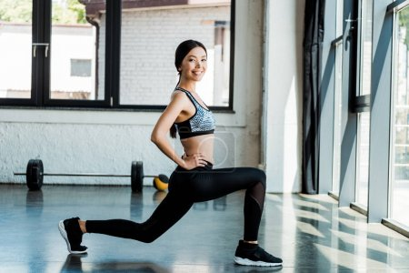 Photo for Cheerful sportswoman doing squat exercise with hand on hip - Royalty Free Image