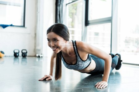Photo for Happy sportswoman doing press ups in gym - Royalty Free Image