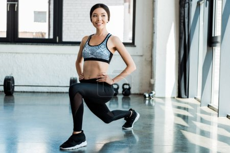 Photo for Cheerful woman in sportswear doing squat exercise with hands on hips - Royalty Free Image