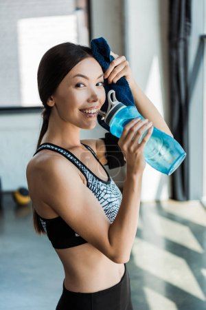Photo for Cheerful young woman holding sport bottle and wiping sweat in sports center - Royalty Free Image