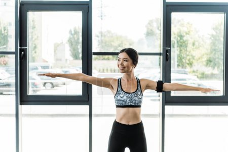 Photo for Positive and athletic woman doing exercise in gym - Royalty Free Image
