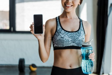 cropped view of cheerful girl holding sport bottle and smartphone with blank screen