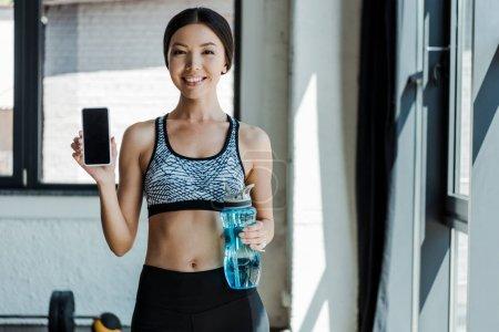 Photo pour Fille gaie tenant bouteille de sport et smartphone avec écran vierge - image libre de droit