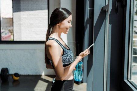 Photo pour Vue latérale d'une jeune femme heureuse utilisant un smartphone et tenant une bouteille de sport - image libre de droit