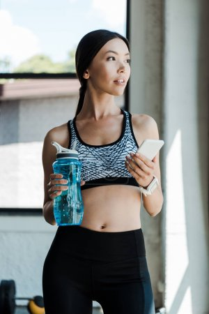 attractive woman using smartphone and holding sport bottle
