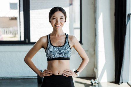 Photo for Happy young woman standing with hands on hips in gym - Royalty Free Image