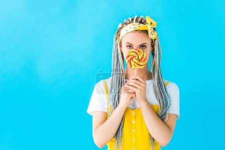 Photo for Beautiful girl with dreadlocks covering face with lollipop isolated on turquoise - Royalty Free Image