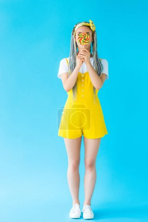 Photo for Girl with dreadlocks covering face with lollipop on turquoise - Royalty Free Image